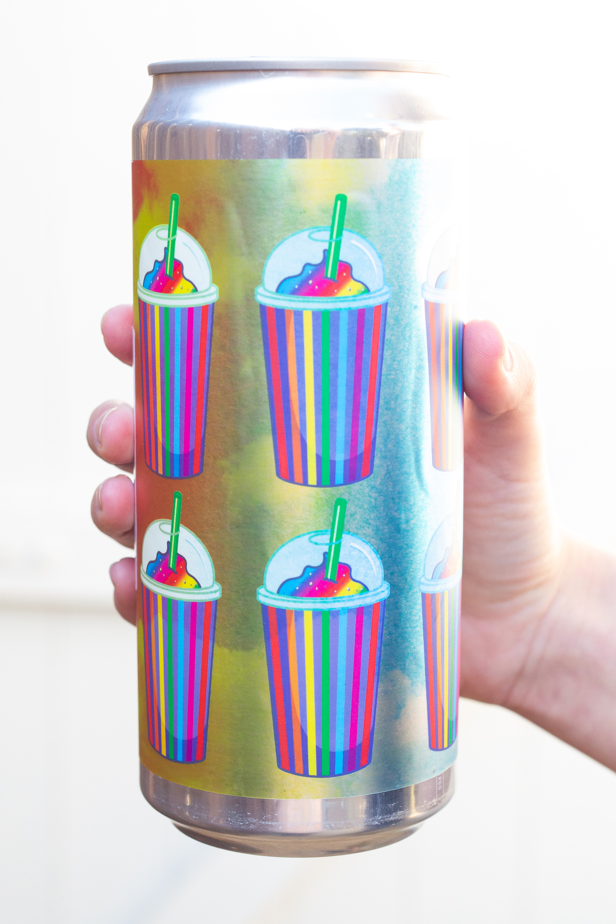 A hand holds and extra large can of beer. It's label is multiple prints of a rainbow slushy.