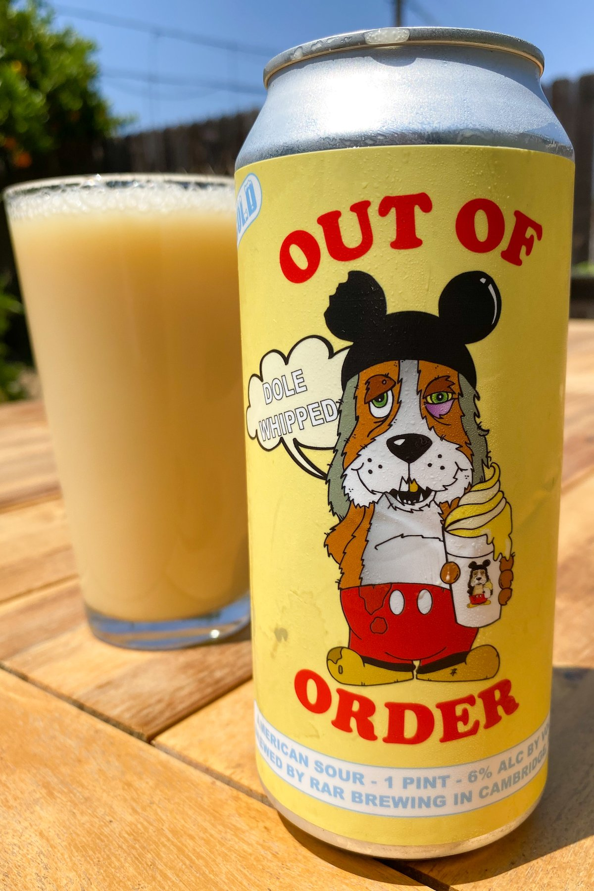 A yellow Out of Order beer can sits in front of a pint glass that the pineapple dole whip beer has been poured into.