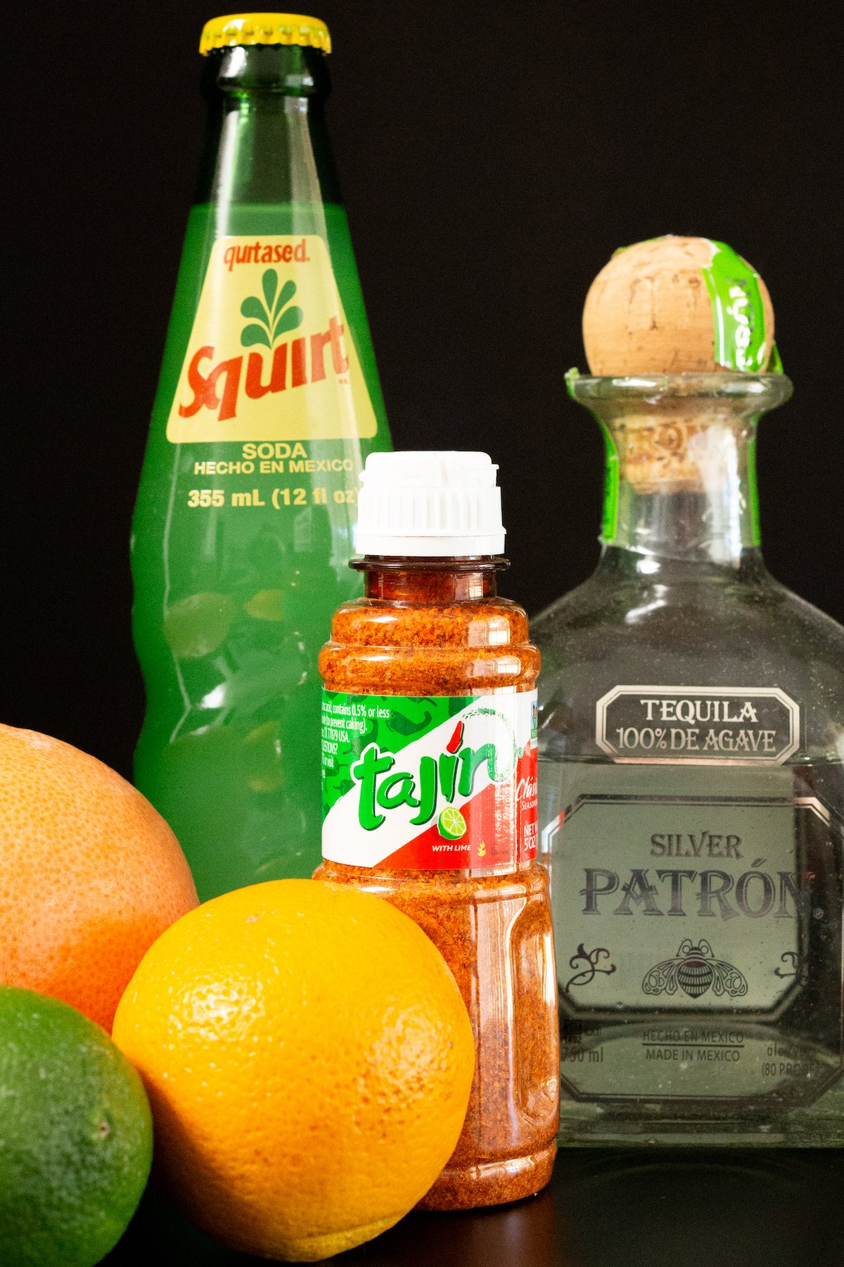 All the ingredients to make a cantarito on a black background: a fresh grapefruit, an orange, a lime, tajin chile salt, squirt soda in a glass bottle, and a bottle of patron.