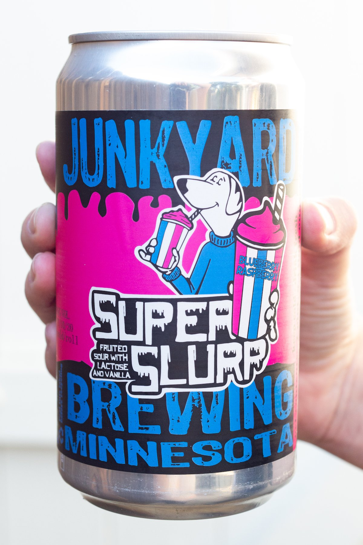 A hand holds up a can of Junkyard Super Slurp sour beer against a white background. The label of the beer is pink and blue and has a polar beer mascot holding a slurpee.