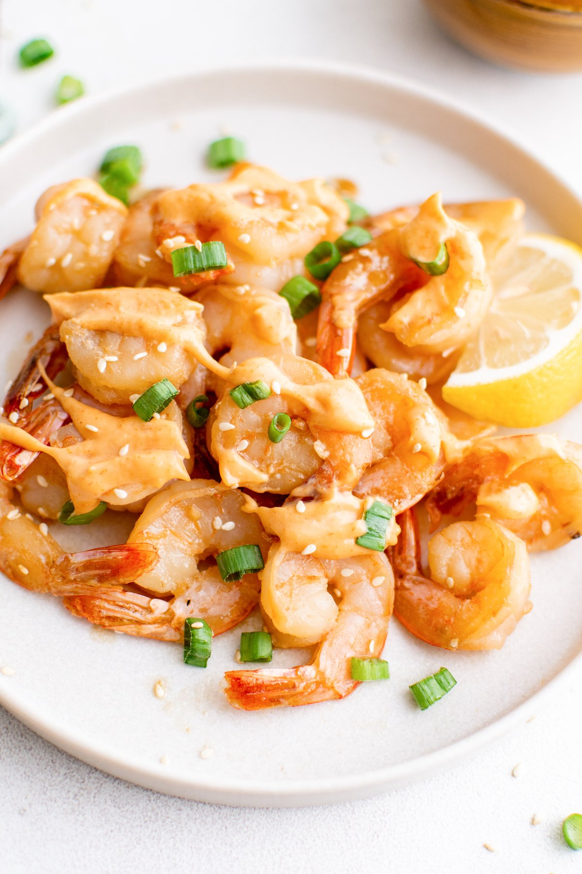 A white dinner plate filled with hibachi shrimp that's been drizzled with yum yum sauce.