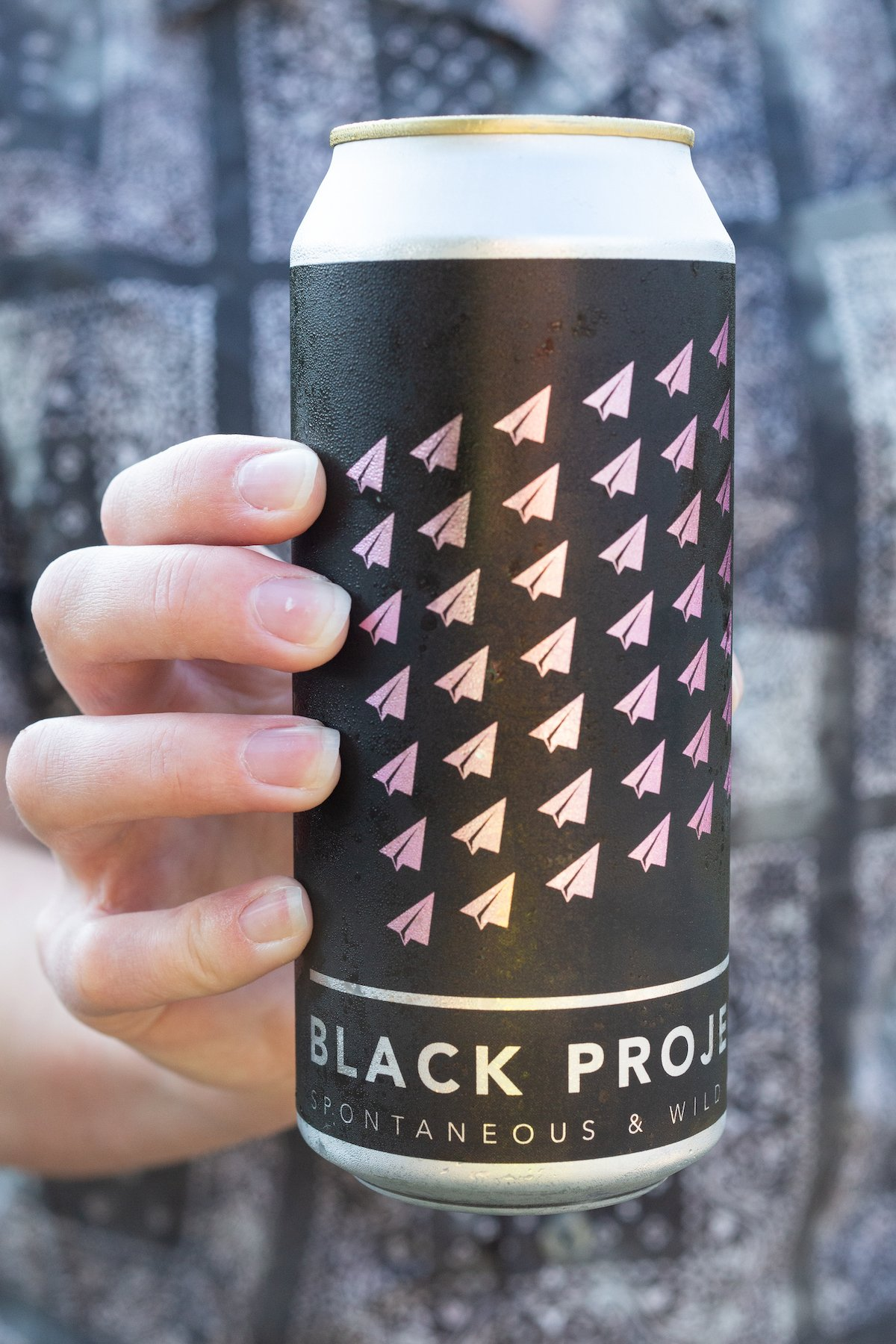 """A hand holds a black beer can that reads """"Black Project Wild & Spontaneous Ales"""""""