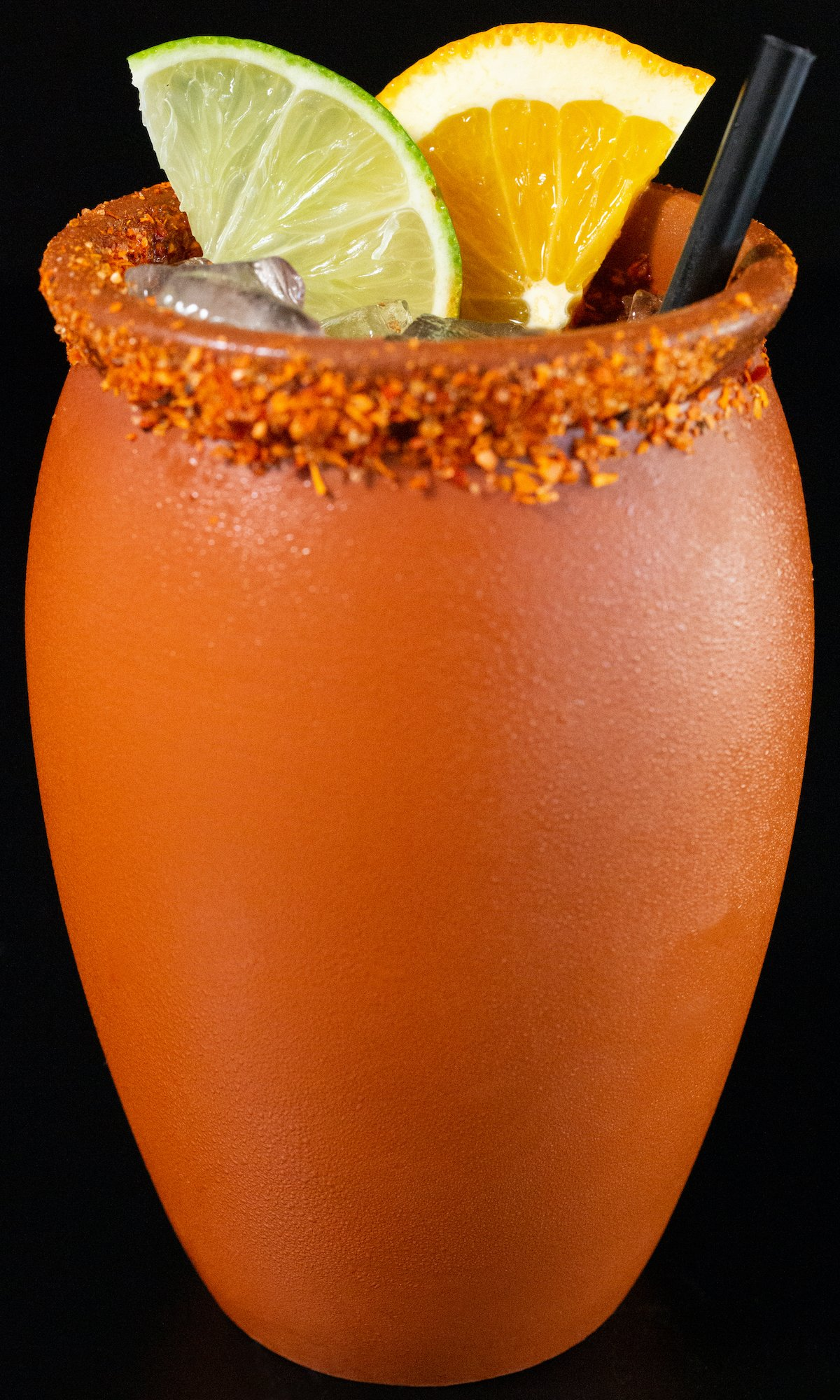 A clay pot filled with a cantarito cocktail sits on a black background. The rim of the pot is covered in chile salt and it is garnished with a lime and orange slice.