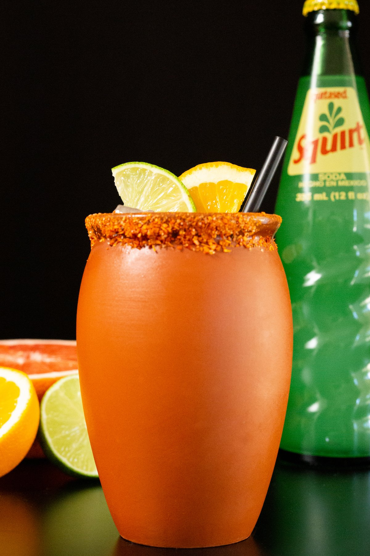 A clay jar that's filled with a cantarito cocktail is garnished with a lime & orange slice. It sits on a black background next to a glass bottle of squirt soda and sliced grapefruit, orange, and lime.