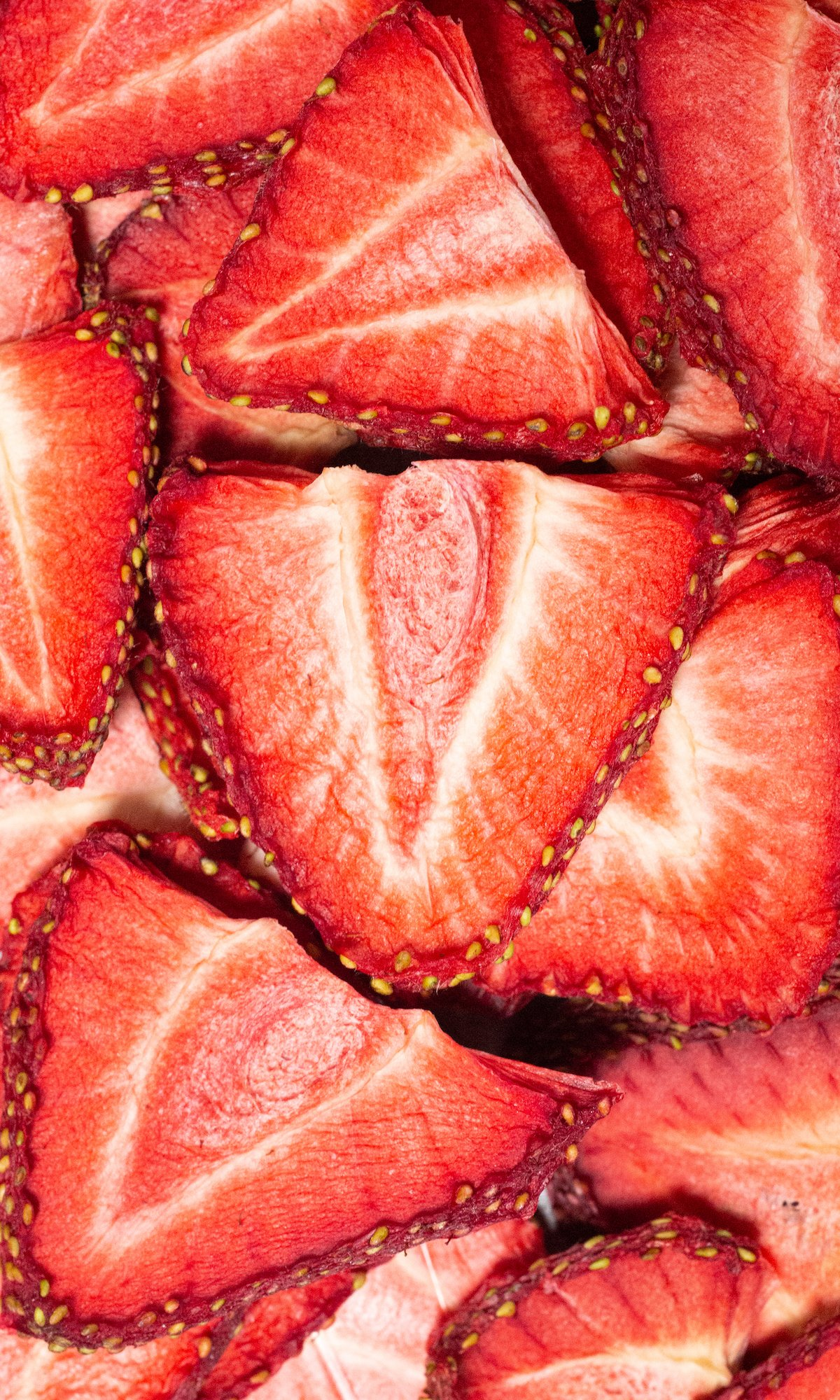 Overhead view of bright red strawberry slices that have been dehydrated.