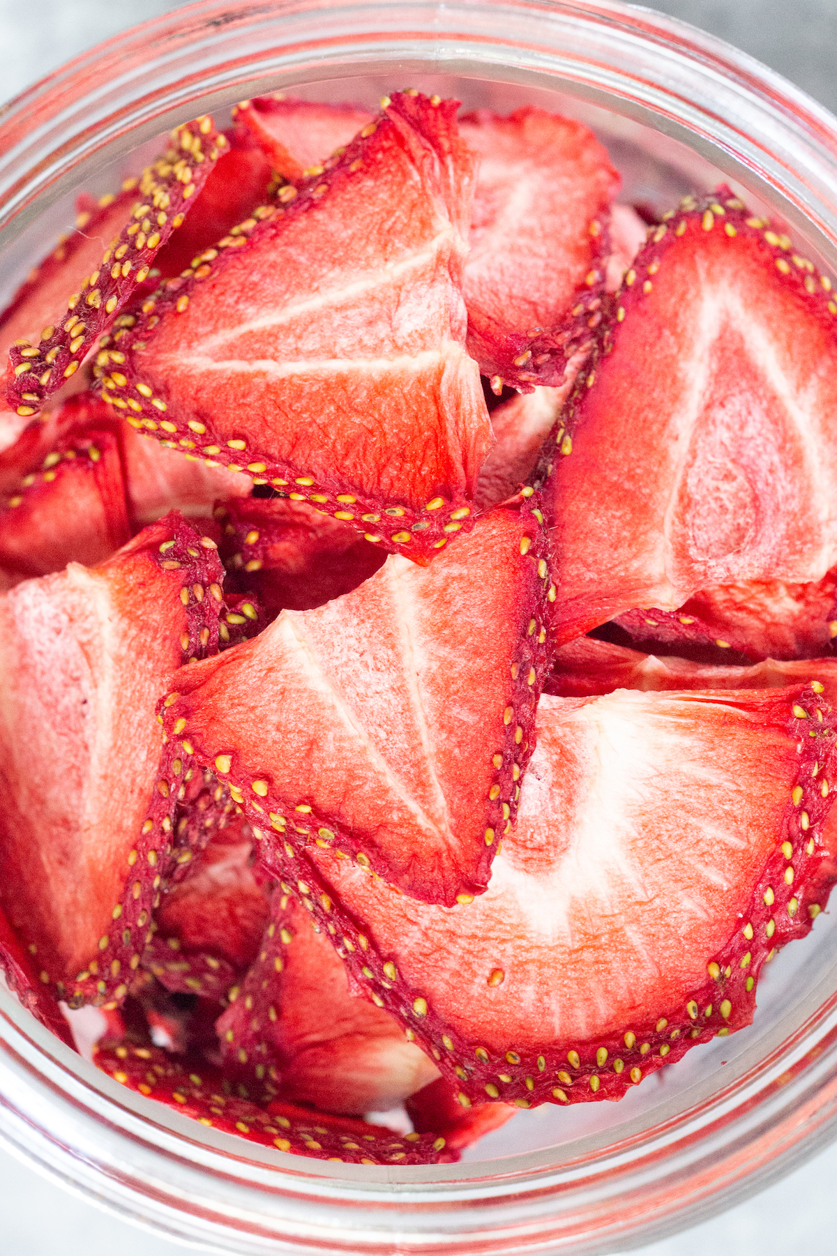 Overhead view of a glass jar that's filled to the top with sliced dehydrated strawberries