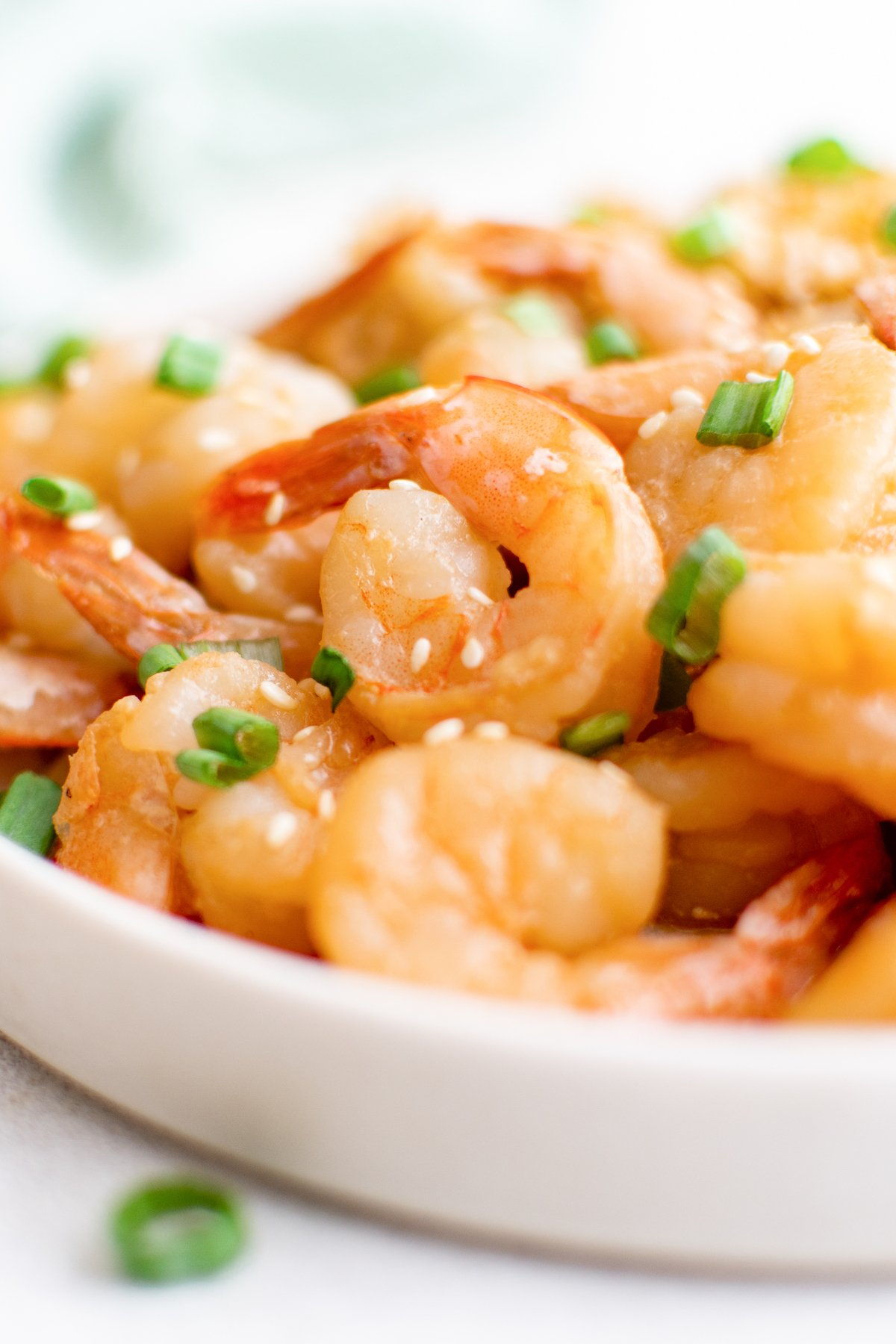 A white plate filled with cooked hibachi shrimp that's covered in sesame seeds and sliced green onions.
