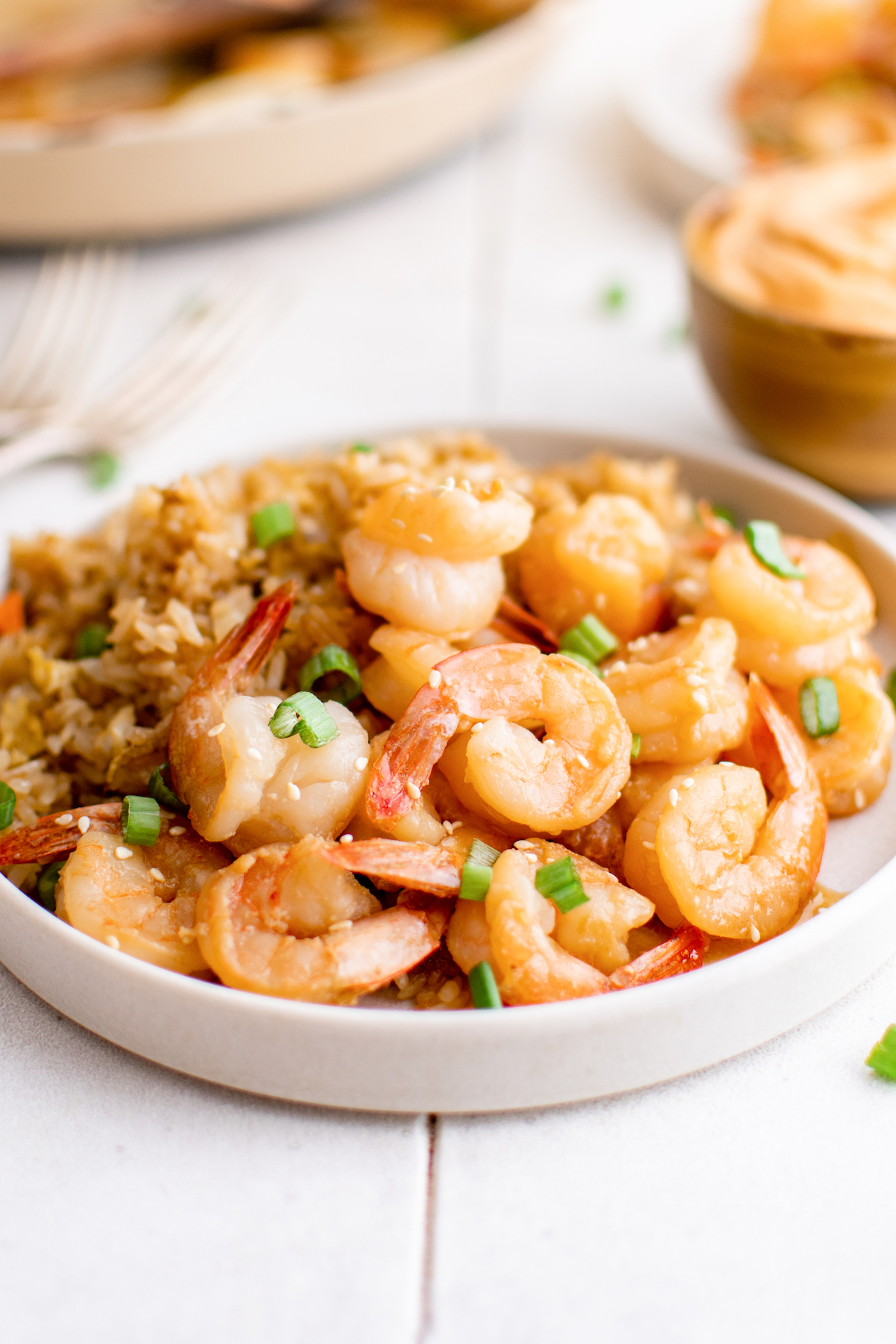 A white serving plate filled with hibachi shrimp. A bowl of yum yum sauce sits in the background.