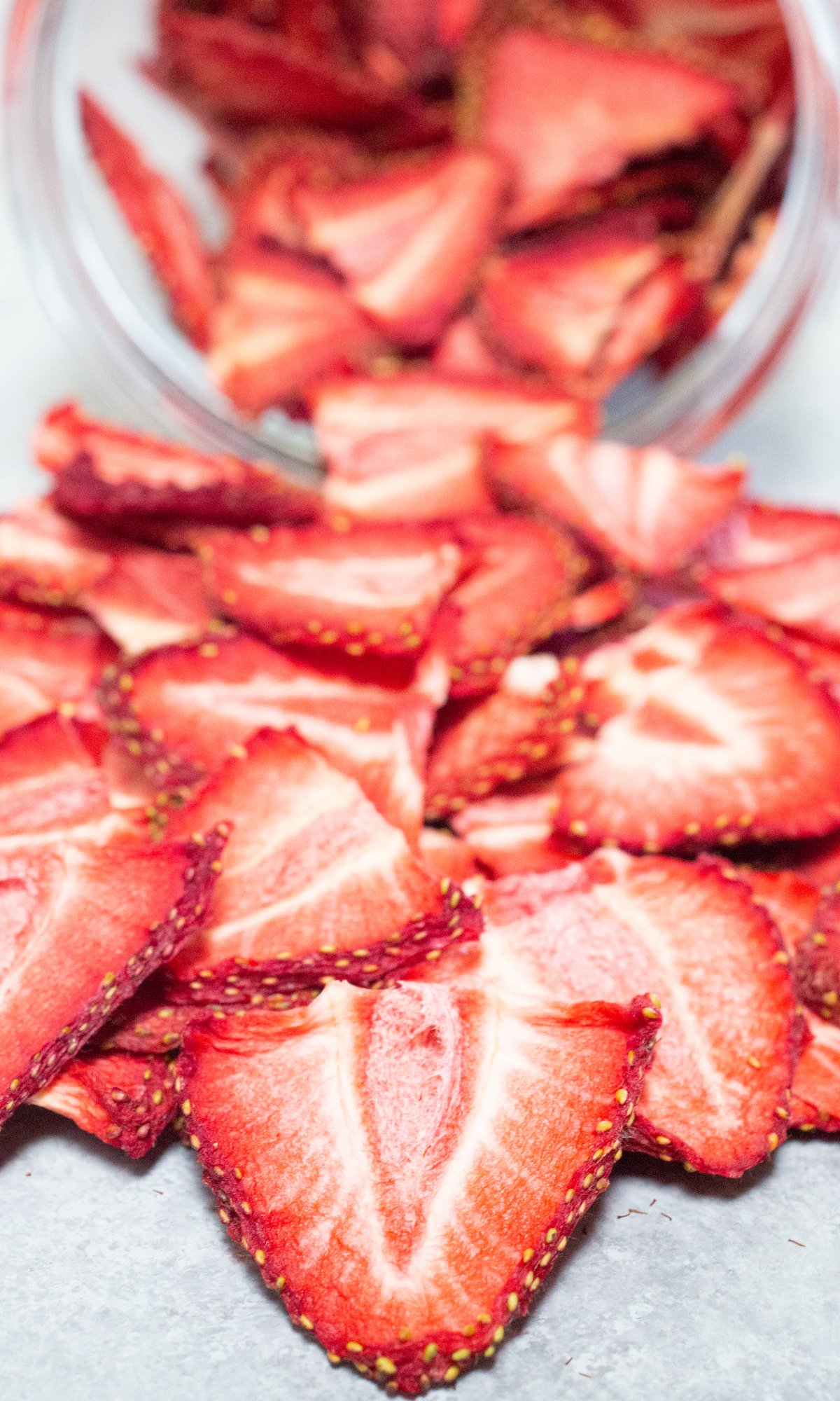 Dehydrated strawberry chips pouring out of a glass jar.