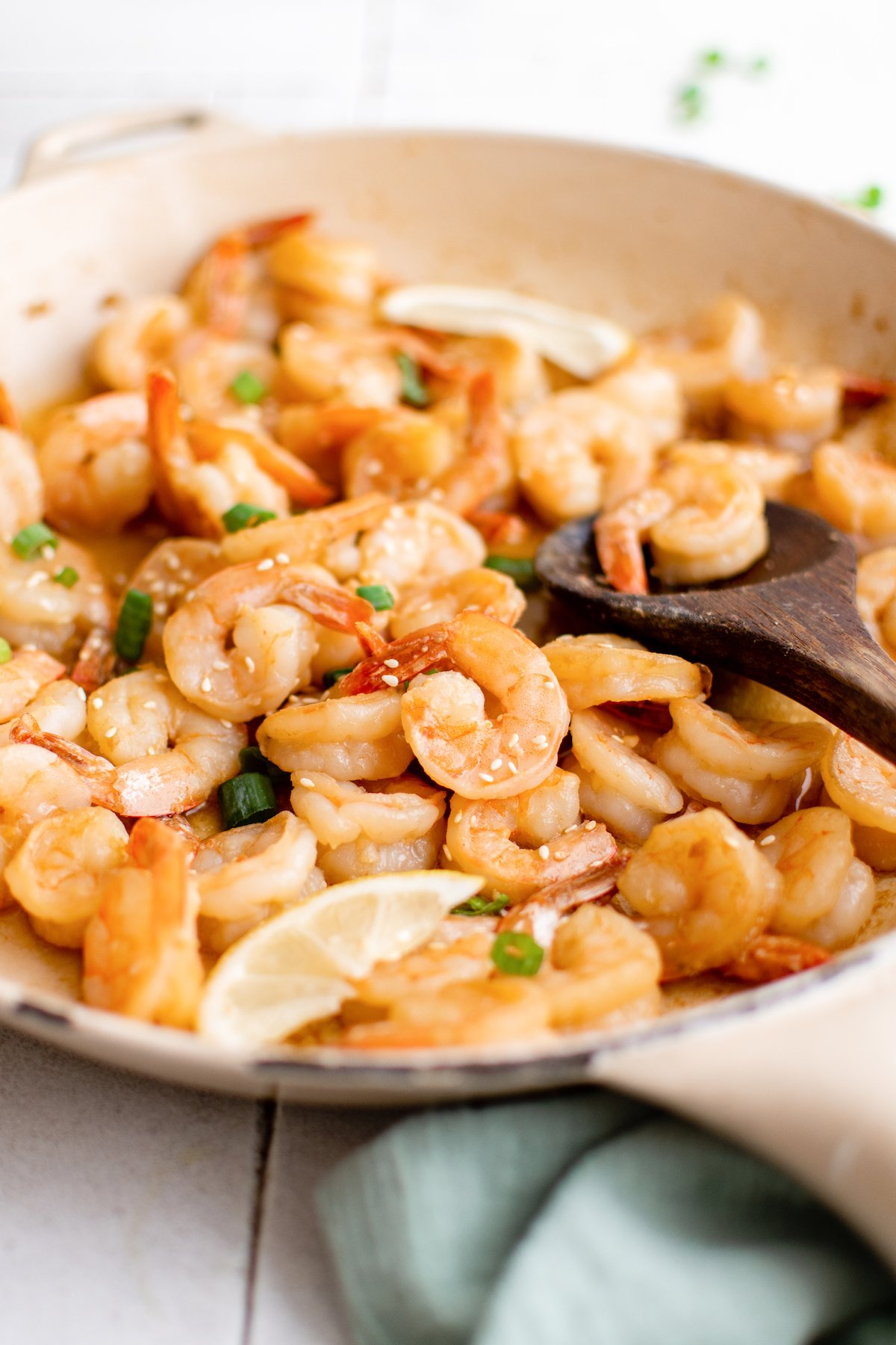 A large pan filled with cooked hibachi shrimp that's garnished with sliced green onions and sesame seeds.