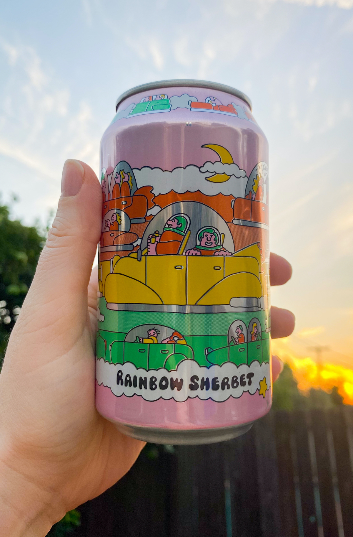 A hand holds a colorful can of rainbow sherbet beer against a sky and sunset background.