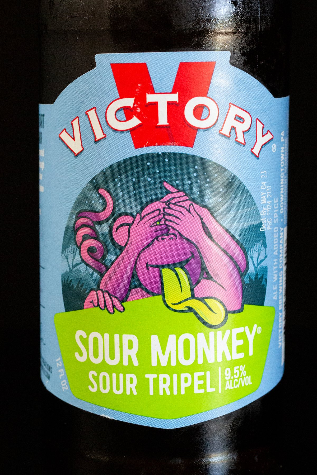 A bottle of Sour Monkey beer on a black background