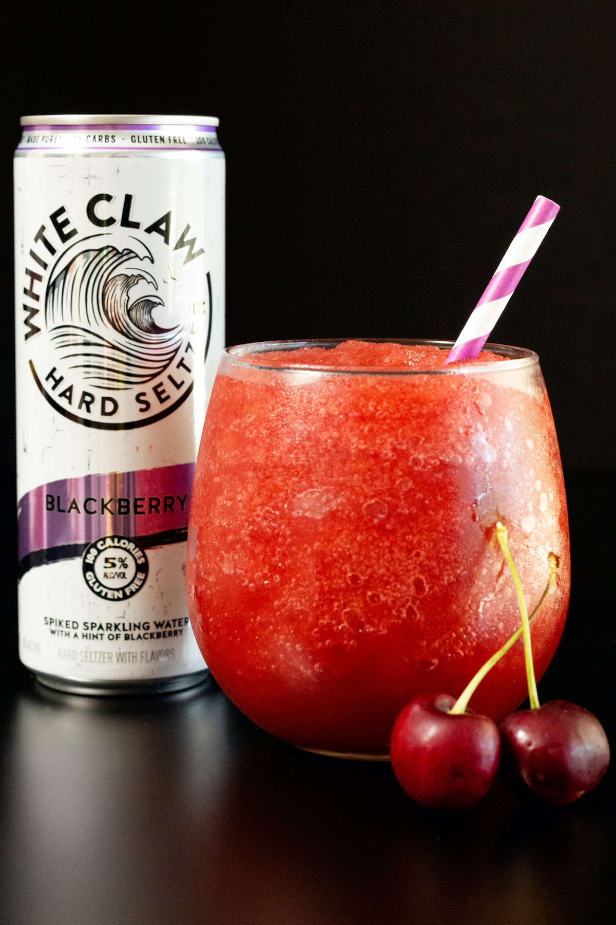 A stemless wine glass filled with a red white claw slushie sits in front of a White Claw can on a black background.
