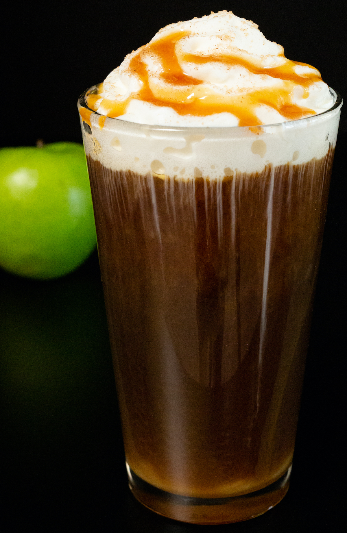 A pint glass filled with cold brew coffee and topped with whipped cream and caramel sits next to a green apple on a black background.