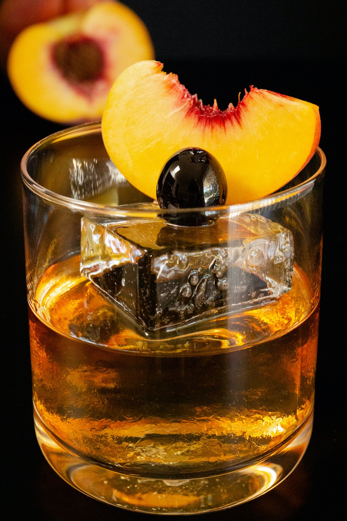 A clear low ball glass is filled halfway with a peach old fashioned. There's a large, clear piece of block ice with a peach slice and maraschino cherry resting on top as garnish.