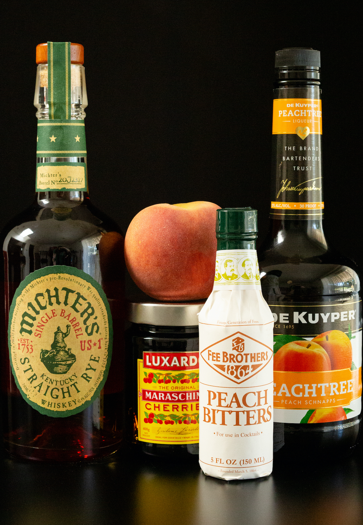 All the ingredients for peach old fashioned sit on a black background. A bottle of Michter's Rye Whiskey, maraschino cherries, peach schnapps, peach bitters, and a fresh peach.