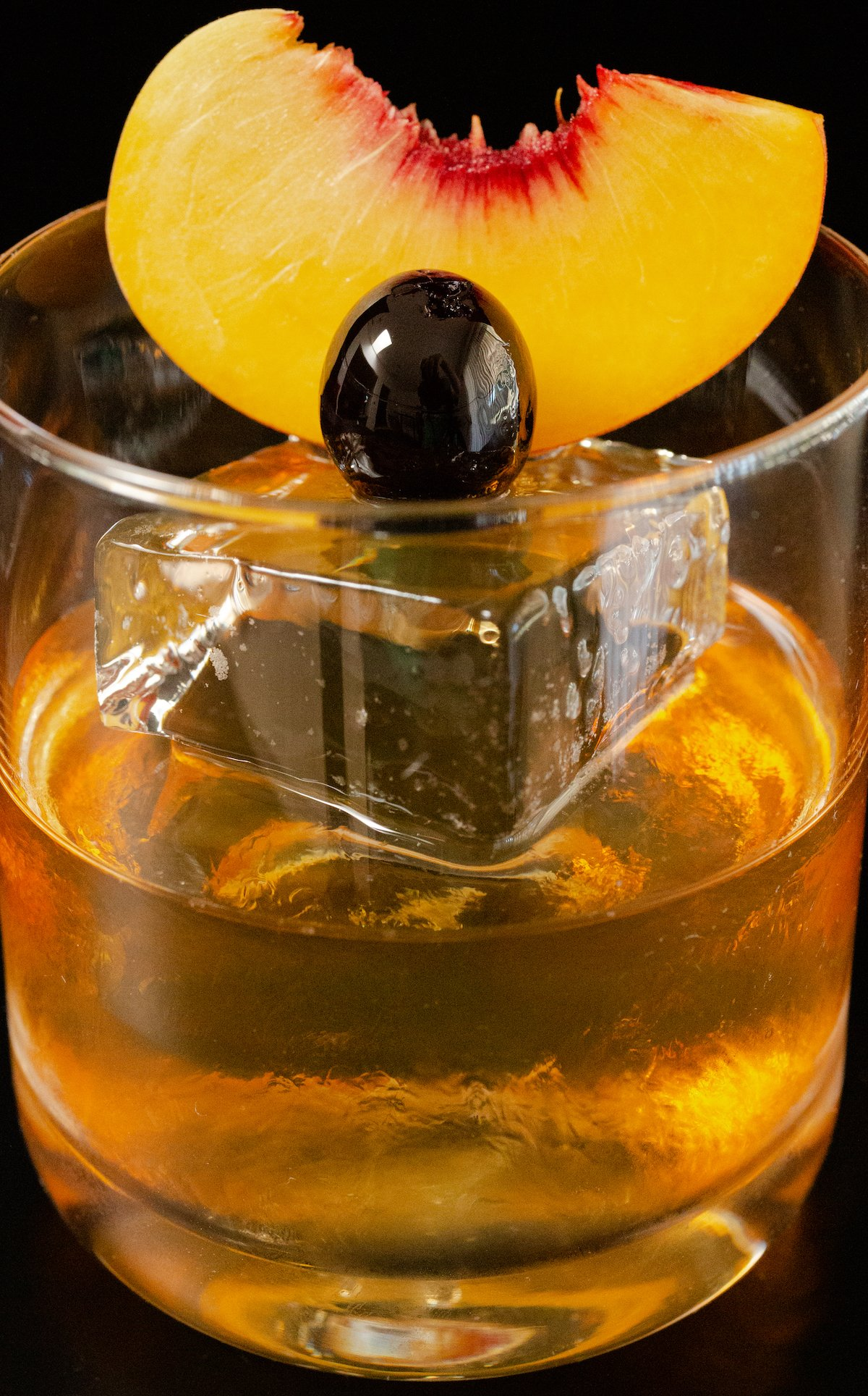 Close up of a clear lowball glass filled with a piece of large block ice, then filled halfway with old fashioned mixture. A peach slice and cherry are garnish.