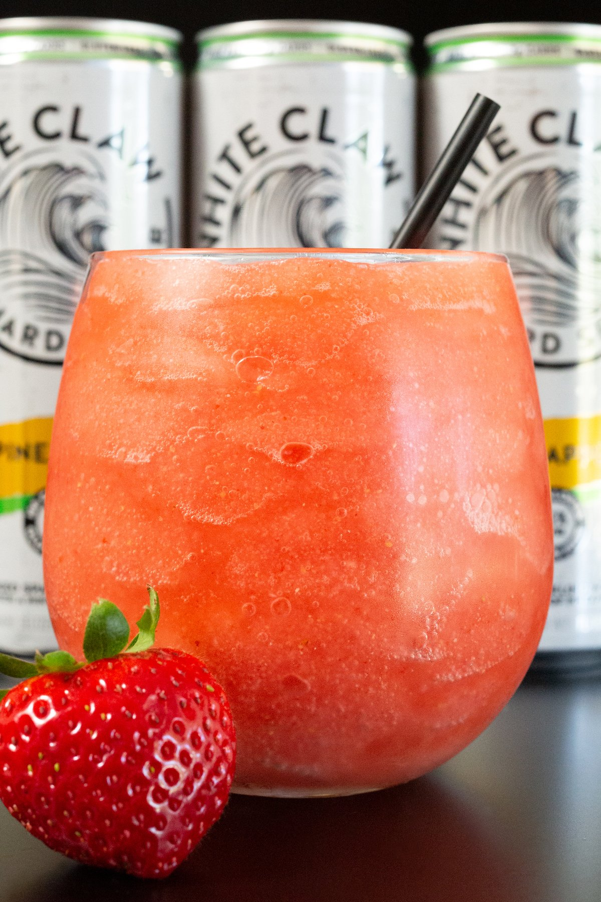 Closeup of a wine glass filled with a pink colored white claw slushie.