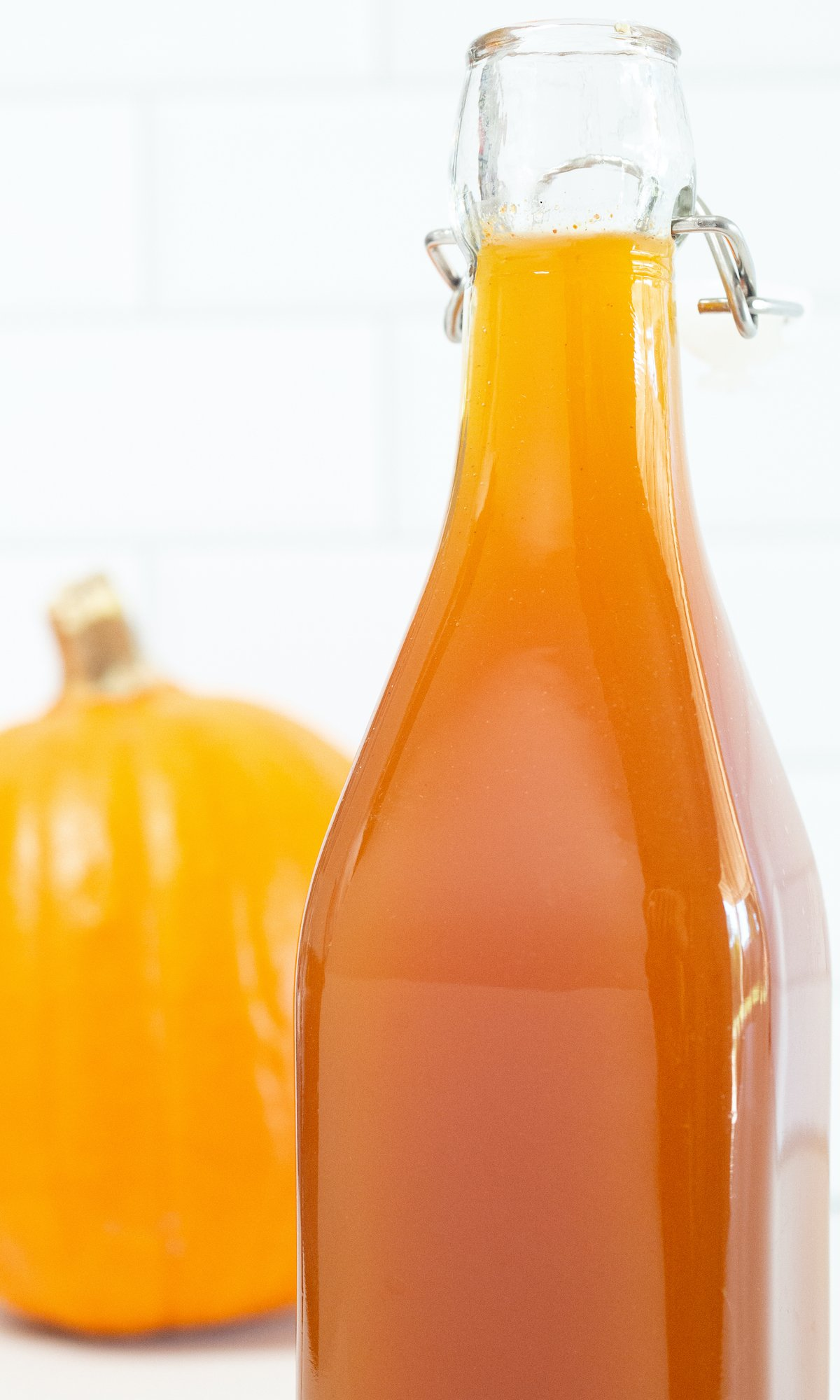 Close up of a bottle of pumpkin spice syrup on a white background next to a pumpkin