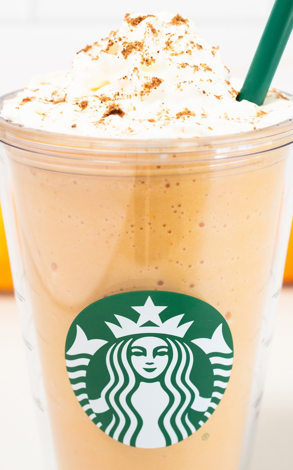 Close up of a starbucks plastic tumbler with a pumpkin spice frappucino and whipped cream on top.