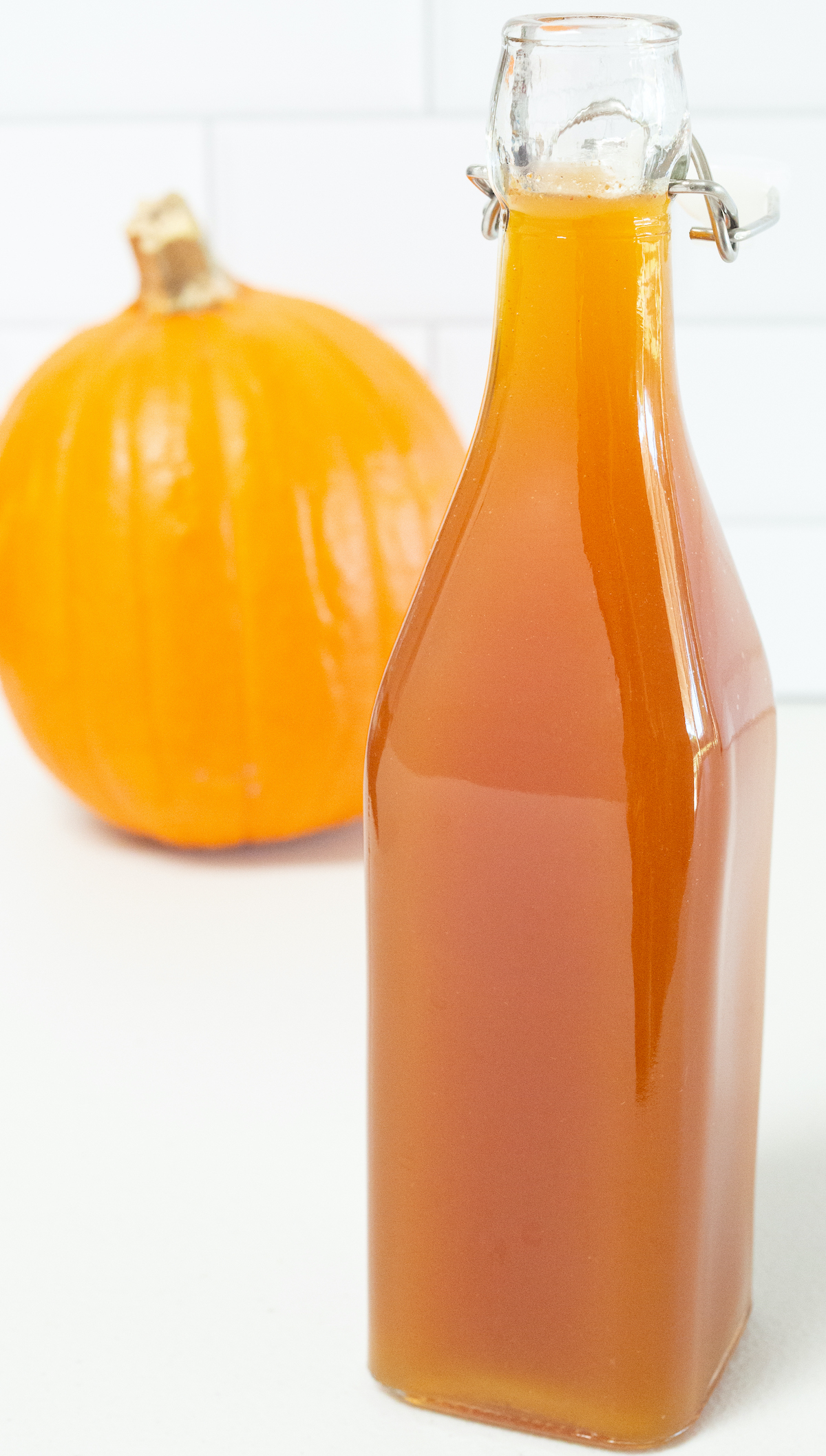 A brownish orange bottle of pumpkin spice syrup is in focus in the foreground, a pumpkin is out of focus in the background.
